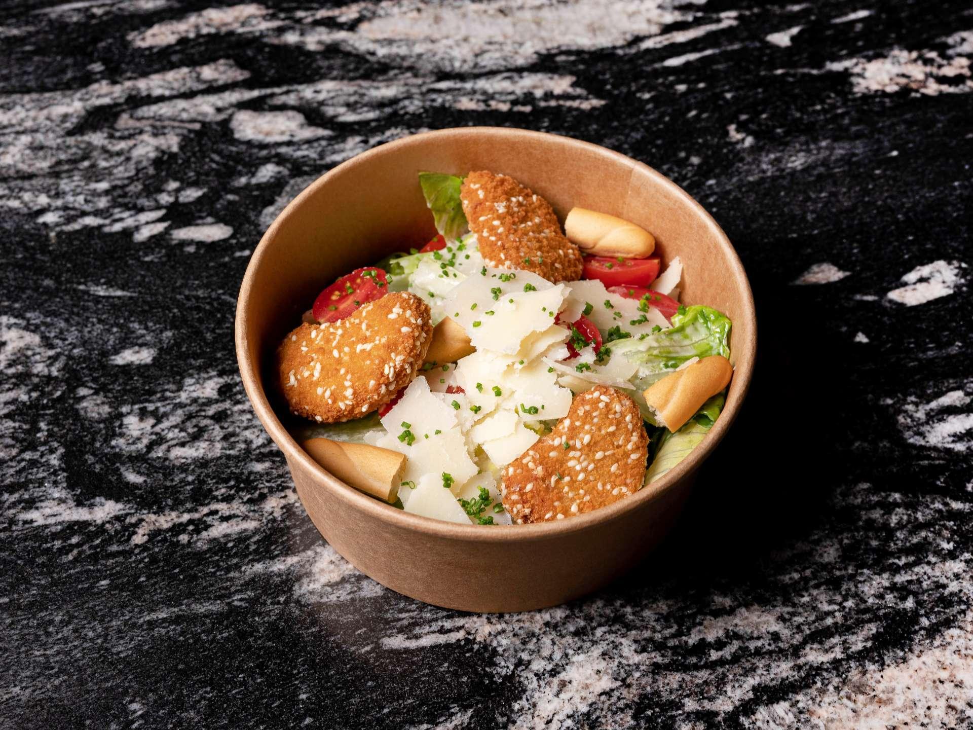 Nuestra ensalada César con parmesano rallado y Nuggets veggies