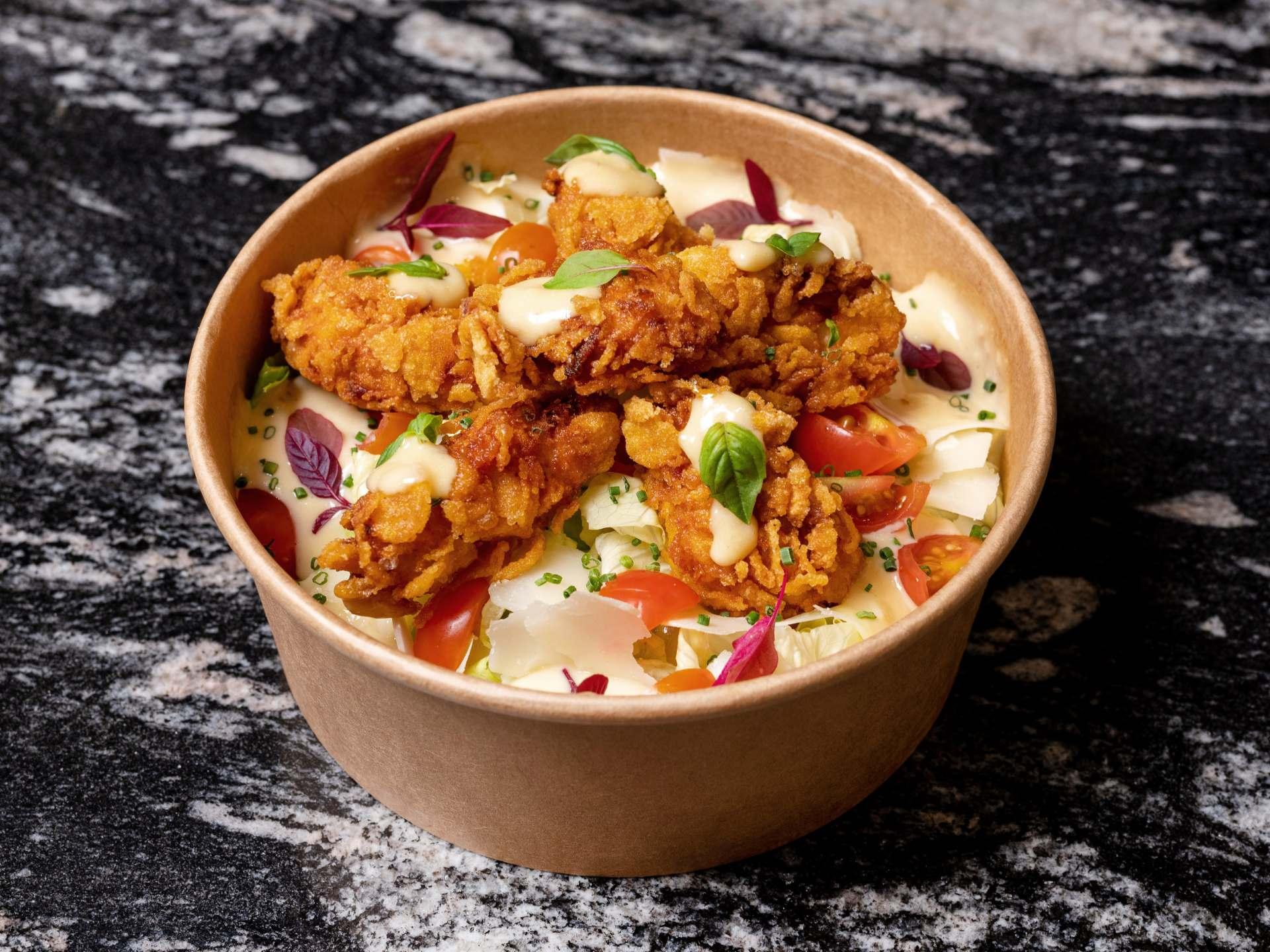 Nuestra ensalada César con parmesano rallado y pollo crujiente